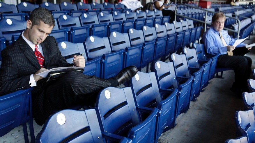 "FILE – In this July 15, 2009, file photo, job seeker Dave Pucci of Berwyn, Pa., looks over notes during a sixth annual ""Grand Slam Career Fair"" as he sits in the stands of Citizens Bank Park in Philadelphia."