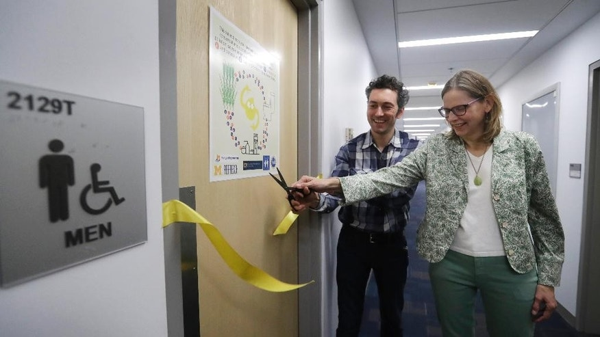 Abe Noe-Hays, director of research at the Vermont-based Rich Earth Institute, left, and Nancy Love, professor of civil and environmental engineering at the University of Michigan cut the ribbon to a men's bathroom with a special toilet at the University of Michigan engineering building, Tuesday, Jan. 24, 2017, in Ann Arbor, Mich. The toilet is part of a multi-state project researching the conversion of human urine into fertilizer. (AP Photo/Carlos Osorio)