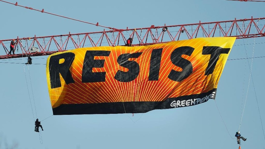 "Protesters unfurl a banner that reads ""Resist"" at the construction site of the former Washington Post building in Washington, Wednesday, Jan. 25, 2017, after police say protesters climbed a crane at the site refusing to allow workers to work in the area. (AP Photo/Pablo Martinez Monsivais)"