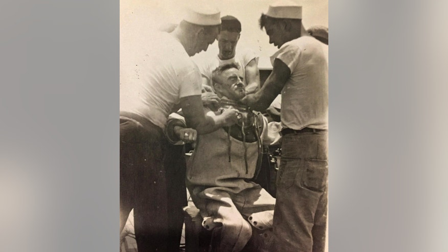 This circa 1943 photo provided by the Hartle family shows Navy diver Ken Hartle getting into his dive suit in Pearl Harbor, Hawaii. Hartle, believed to be the oldest surviving salvage diver who worked the wreckage left after the Japanese attack on Pearl Harbor in World War II, died Tuesday, Jan. 24, 2017. He was 103. (Courtesy Hartle Family via AP)