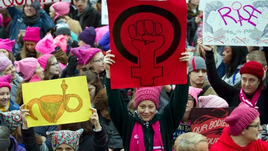Jan. 21, 2017: Women with bright pink hats and signs gather early and are set to make their voices heard on the first full day of Donald Trump's presidency.