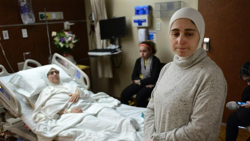 Nour Ulayyet foreground, looks on after her sister Sahar Algonaimi was not permitted to enter the United States while comforting her mother Isaaf Jamal Eddin at Munster Community Hospital Saturday, Jan. 28, 2017, in Munster, Ind. Ulayyet of Valparaiso, Ind., said her sister, a Syrian living in Saudi Arabia who had a valid visa, was sent back after arriving from Riyadh at Chicago's O'Hare International Airport on Saturday and told she couldn't enter the U.S. to help care for their sick mother following President Donald Trump's executive order banning individuals from certain Muslim-majority countries from entering the U.S.  (AP Photo/Paul Beaty)