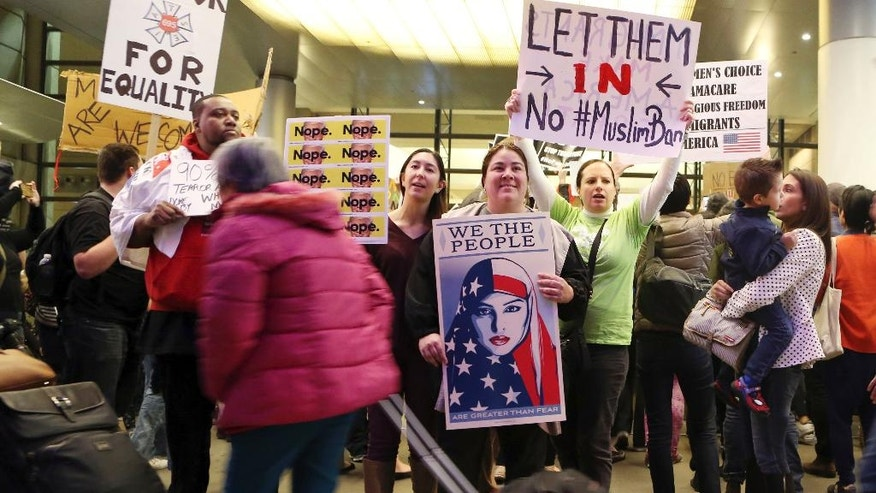 Travelers pass people opposed to President Donald Trump's executive order barring entry to the U.S. by Muslims from certain countries demonstrating at the Tom Bradley International Terminal at Los Angeles International Airport Saturday, Jan. 28, 2017, in Los Angeles.  (AP Photo/Reed Saxon)