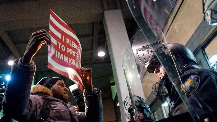 A protester stands facing police officers at an entrance of Terminal 4 at John F. Kennedy International Airport in New York, Saturday, Jan. 28, 2017,  after earlier in the day two Iraqi refugees were detained while trying to enter the country. On Friday, Jan. 27, President Donald Trump signed an executive order suspending all immigration from countries with terrorism concerns for 90 days. Countries included in the ban are Iraq, Syria, Iran, Sudan, Libya, Somalia and Yemen, which are all Muslim-majority nations. (AP Photo/Craig Ruttle)