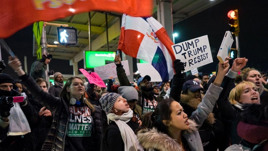 Protesters block an intersection near Terminal 4 at John F. Kennedy International Airport in New York, Saturday, Jan. 28, 2017, after earlier in the day two Iraqi refugees were detained while trying to enter the country. On Friday, Jan. 27, President Donald Trump signed an executive order suspending all immigration from countries with terrorism concerns for 90 days. Countries included in the ban are Iraq, Syria, Iran, Sudan, Libya, Somalia and Yemen, which are all Muslim-majority nations. (AP Photo/Craig Ruttle)