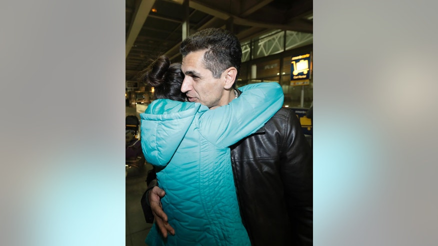 Mahdi Radgoudarzi, right, of Sacramento, Calif., is hugged by his daughter Niloofar Radgoudarzi arrived from Tehran, Iran, at San Francisco International Airport Saturday, Jan. 28, 2017, in San Francisco. President Donald Trump's executive order bars citizens of seven predominantly Muslim-majority countries from entering the U.S. Radgoudarzi was held for a few hours then eventually allowed to enter the country. (AP Photo/Marcio Jose Sanchez)