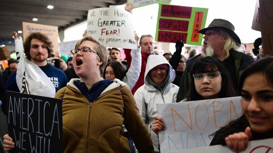 Natalie Swarts of Philadelphia calls out protest chants as the crowd follows in cadence during a protest of President Donald Trump's travel ban on refugees and citizens of seven Muslim-majority nations, Sunday, Jan. 29, 2017, at Philadelphia International Airport in Philadelphia. (AP Photo/Corey Perrine)