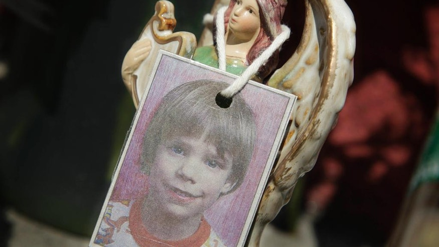 FILE- In this May 28, 2012, file photo, a photograph of Etan Patz hangs on an angel figurine, which is part of a makeshift memorial in the SoHo neighborhood of New York. Prosecutors once again must sum up their case against a man accused of killing Patz in New York City 37 years ago. Closing arguments in the case against Pedro Hernandez began Monday, Jan. 30, 2017, in Manhattan and were set to continue Tuesday. (AP Photo/Mark Lennihan, File)