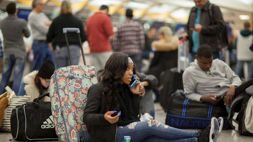 A Delta passenger sits on the floor while waiting in line at Hartsfield-Jackson International Airport after Delta Air Lines grounded all domestic flights due to automation issues, Sunday, Jan. 29, 2017, in Atlanta. (AP Photo/Branden Camp)