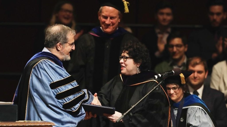 University of Michigan President Mark Schlissel presents Supreme Court Justice Sonia Sotomayor, a Doctor of Laws degree, Monday, Jan. 30, 2017, during a ceremony at the university in Ann Arbor, Mich. (AP Photo/Carlos Osorio)
