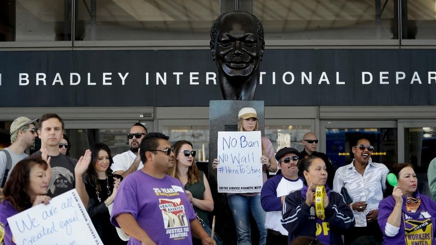 Demonstrators chant outside Tom Bradley International Terminal during a protest by airport service workers from United Service Workers West union Monday, Jan. 30, 2017, at Los Angeles International Airport. The vigil in support of travelers affected by the executive order restricting travel from seven primarily Muslim countries. (AP Photo/Chris Carlson)