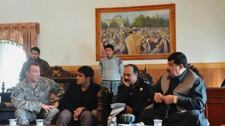 In this 2010 photo provided by U.S. Army Capt. Matthew Ball shows his interpreter Qismat Amin, second seated from left, in Jalalabad, the capital of Nangarhar province of Afghanistan. Amin, who has been living in hiding after getting threats from Taliban and Islamic state fighters, got his visa Sunday, Jan. 29, 2017, after nearly four years of interviews. Ball bought him a $1,000 plane ticket to San Francisco and plans to meet him at the airport with an attorney. Ball said he has bought a plane ticket for his Afghan translator in case that country is added to the list of banned nations. ( U.S. Army Capt. Matthew Ball via AP)