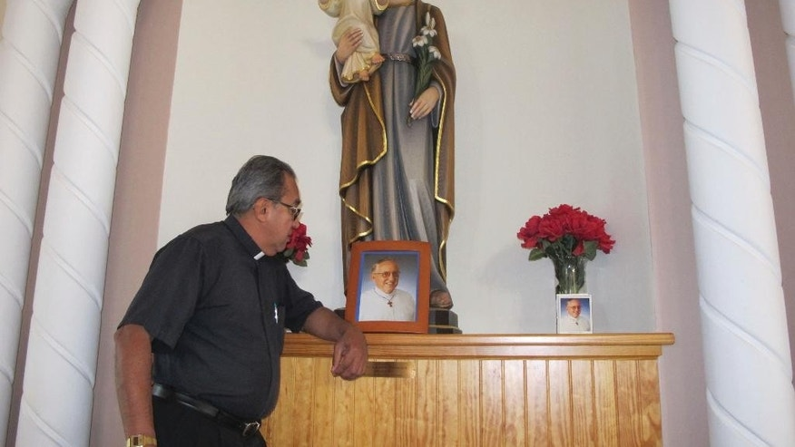 In this Jan. 17, 2017 photo, Father Heriberto Vergara looks at a photograph of his slain colleague, Father Rene Robert in St. Augustine, Fla. Last summer, after a multi-state manhunt that started in Florida and stretched to South Carolina, police arrested Steven Murray in connection with the 71-year-old Robert's killing. Murray led authorities into the Georgia woods, where Robert's body lay. Police said Murray had asked Father Rene for a ride, then kidnapped and fatally shot him. Prosecutors plan to seek the death penalty, a decision that Catholic officials from Georgia and Florida plan to protest on the courthouse steps. (AP Photo/Jason Dearen)