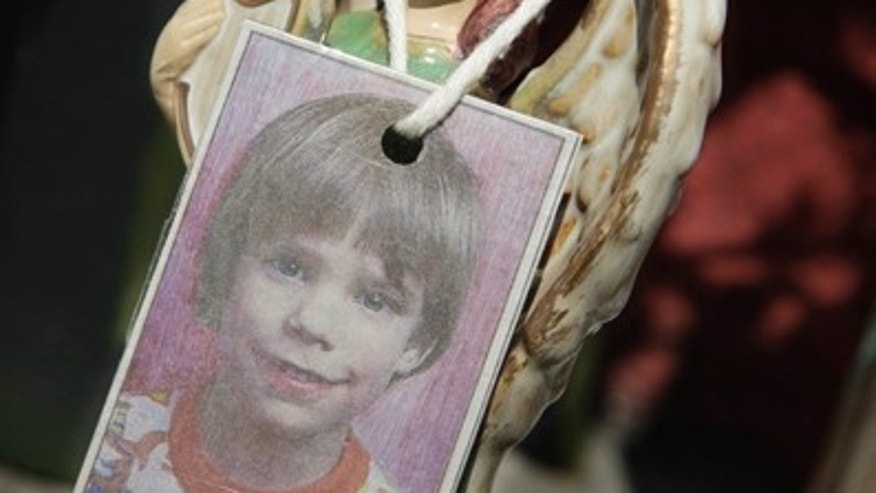 A photograph of Etan Patz hangs on an angel figurine, part of a memorial in his honor.