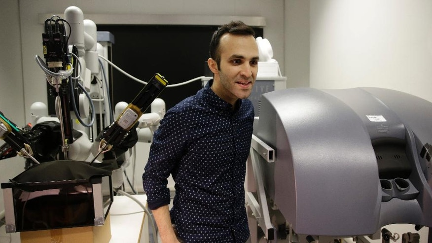 Iranian-born bioengineer researcher Nima Enayati stands as he works on a robotic surgery machine during an interview with the Associated Press at the Polytechnic University of Milan, Italy, Tuesday, Jan. 31, 2017. An Iranian researcher at Milan's Polytechnic University, Enayati was refused check-in Monday at Milan's Malpensa Airport for his U.S.-bound flight on Turkish Airlines after the Trump administration's executive order came down. (AP Photo/Luca Bruno)