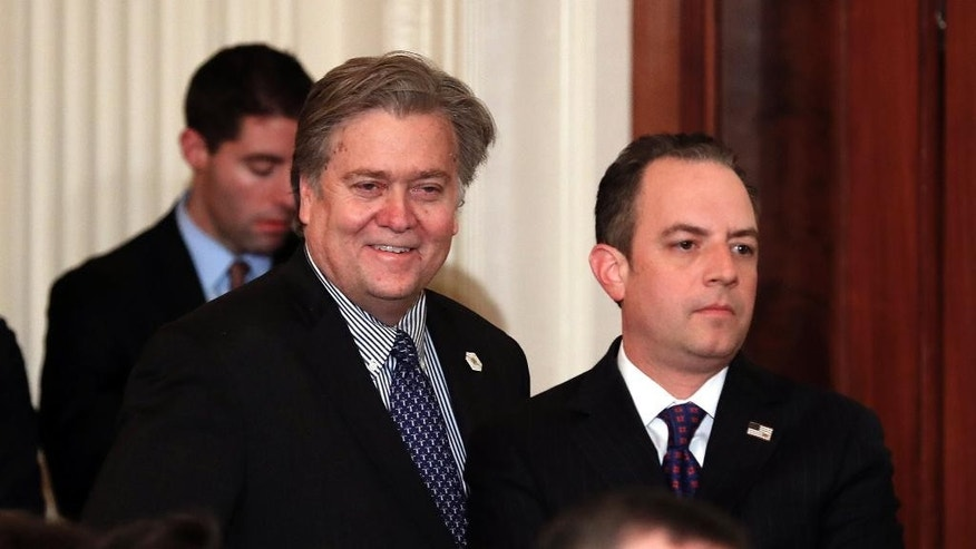 In this Jan. 31, 2017, photo, Steve Bannon, chief White House strategist to President Donald Trump, left, and White House Chief of Staff Reince Priebus stand in the East Room of the White House in Washington before President Donald Trump arrived to announce Judge Neil Gorsuch as his nominee for the Supreme Court. The Trump administration is playing down the significance of a National Security Council restructuring. But the president is treading new ground in making Bannon a regular at NSC meetings.  (AP Photo/Carolyn Kaster)