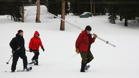 Frank Gehrke, right, chief of the California Cooperative Snow Surveys Program for the Department of Water Resources, carries the snowpack measuring tube as he crosses a snow covered meadow while conducting the second manual snow survey of the season at Phillips Station Thursday, Feb. 2, 2017, in Echo Summit, Calif.   (AP Photo/Rich Pedroncelli)