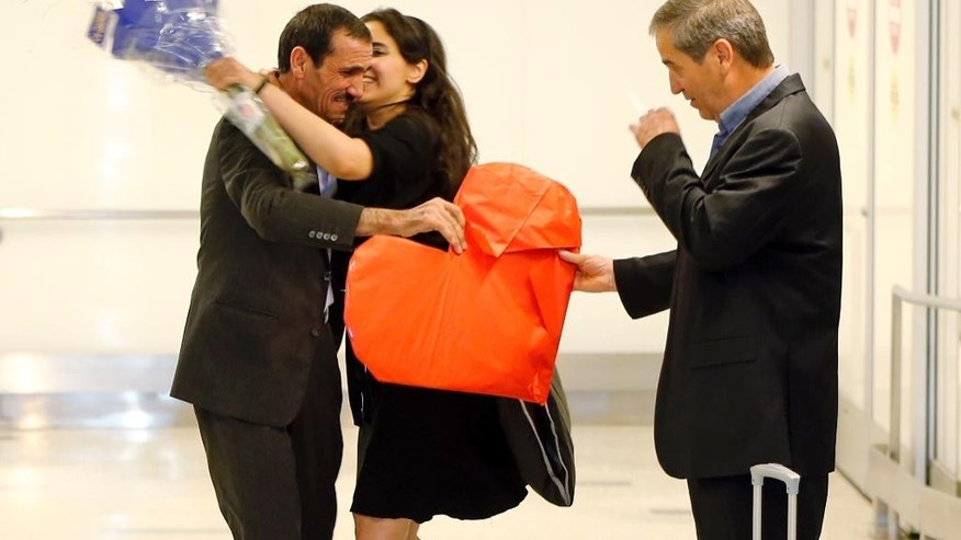 Ali Vayeghan, an Iranian citizen with a valid U.S. visa, left, is kissed by his niece Marjan Vayghan, as his brother Houssein Vayghan welcomes his as he arrives at Los Angeles International Airport Thursday, Feb. 2, 2017. An Iranian man turned away from Los Angeles International Airport under President Donald Trump's executive order barring people from seven Muslim-majority nations has arrived back in the U.S. under a federal judge's order. (AP Photo/Damian Dovarganes)