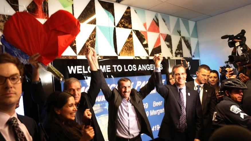 Ali Vayeghan, an Iranian citizen with a valid U.S. visa, fourth from left, lifts his arms with his brother Houssein Vayghan, third from left, and Los Angeles by Los Angeles Mayor Eric Garrett, right, as he is welcomed at Los Angeles International Airport Thursday, Feb. 2, 2017. Second from left is his niece, Marjan Vayghan. An Iranian man turned away from Los Angeles International Airport under President Donald Trump's executive order barring people from seven Muslim-majority nations has arrived back in the U.S. under a federal judge's order. (AP Photo/Damian Dovarganes)