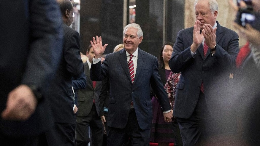 Secretary of State Rex Tillerson, center, accompanied by acting Secretary of State Tom Shannon, right, waves as he arrives to speak to State Department employees at the State Department in Washington, Thursday, Feb. 2, 2017. (AP Photo/Andrew Harnik)
