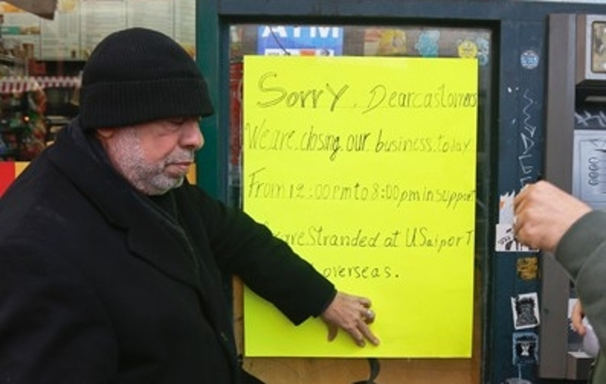 Zamood Zokari, left, and Ali Elazab, right, post a sign on a window of Zokari' family deli in lower Manhattan, alerting customers that the store will close because of a protest against President Donald Trump's travel ban, Thursday, Feb. 2, 2017, in New York. Yemeni business owners who operate corner bodegas and neighborhood delis shut them down on Thursday in protest of the travel ban on people hailing from seven Muslim-majority countries including Yemen. (AP Photo/Bebeto Matthews)