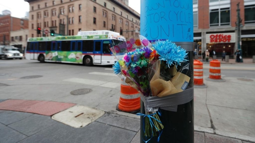 A makeshift memorial put up by Denver Police is affixed to a pole early Wednesday, Feb. 1, 2017, near the scene where a contract transit security officer was shot and killed late Tuesday, Jan. 31 in Denver. Police have not released any details about the shooting, which took place by the city's main transit hub, Union Station. (AP Photo/David Zalubowski)