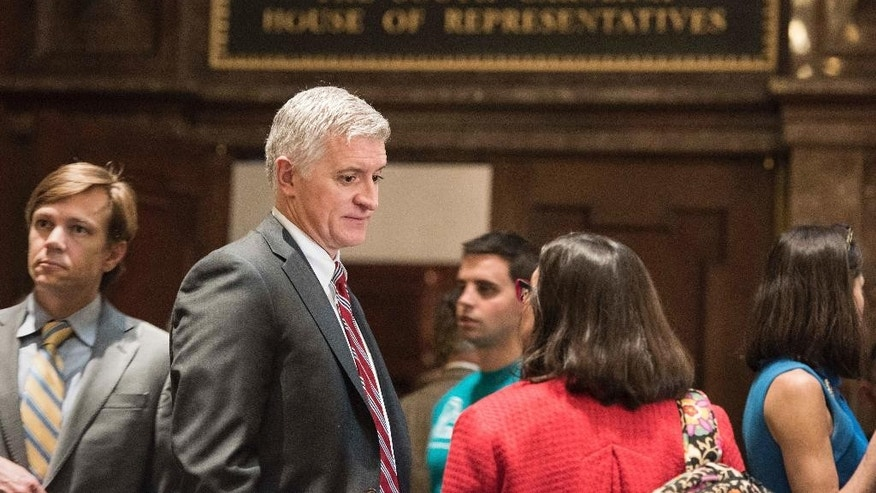 Rep. Jason Elliott, R-Greenville, second from left, and attorney Deb Tedeschi, second from right, talk outside of the House chamber Wednesday, Jan. 18, 2017, in Columbia, S.C. Recently elected in November, Elliott is a 46-year old attorney and South Carolina's first openly gay legislator. (AP Photo/Sean Rayford)