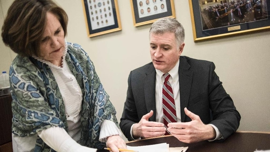 Rep. Jason Elliott, R-Greenville, right, discusses paperwork with Executive Assistant Doris Taylor, left, at the state capitol Wednesday, Jan. 18, 2017, in Columbia, S.C. Recently elected in November, Elliott is a 46-year old attorney and South Carolina's first openly gay legislator. (AP Photo/Sean Rayford)