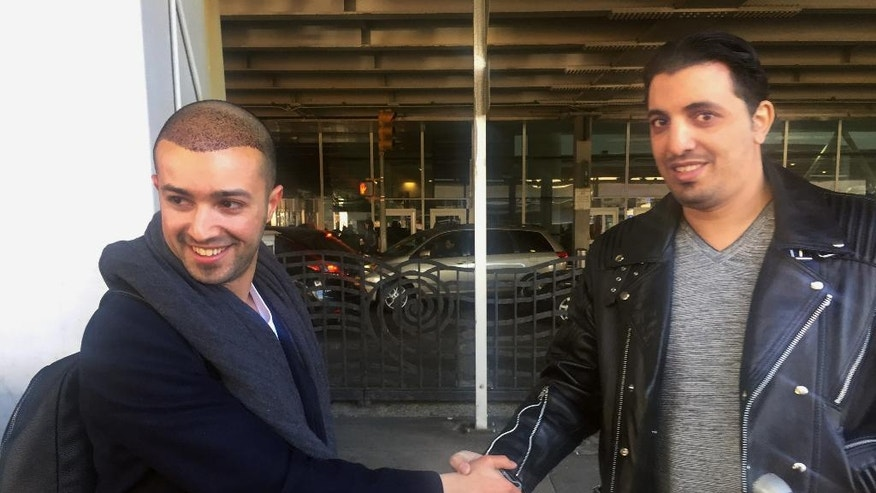 Ammar Alnajjar, left, shakes hands with his cousin, Fahd Alfakih, after coming into New York's JFK International Airport on a flight from Istanbul, Turkey, Saturday, Feb. 4, 2017. The government on Saturday suspended enforcement of President Donald Trump's refugee and immigration ban, enabling Alnajjar to return from Turkey where he was visiting his wife. (AP Photo/William Mathis)