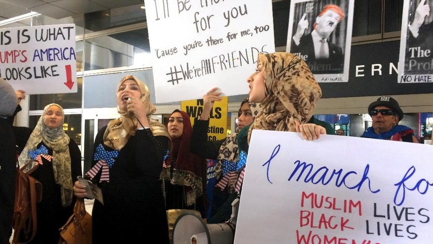 Protesters against President Trump's temporary travel ban on citizens from seven Muslim-majority nations stand in front of the Bradley Terminal at Los Angeles International Airport, Saturday, Feb. 4, 2017, in Los Angeles. (AP Photo/Reed Saxon)