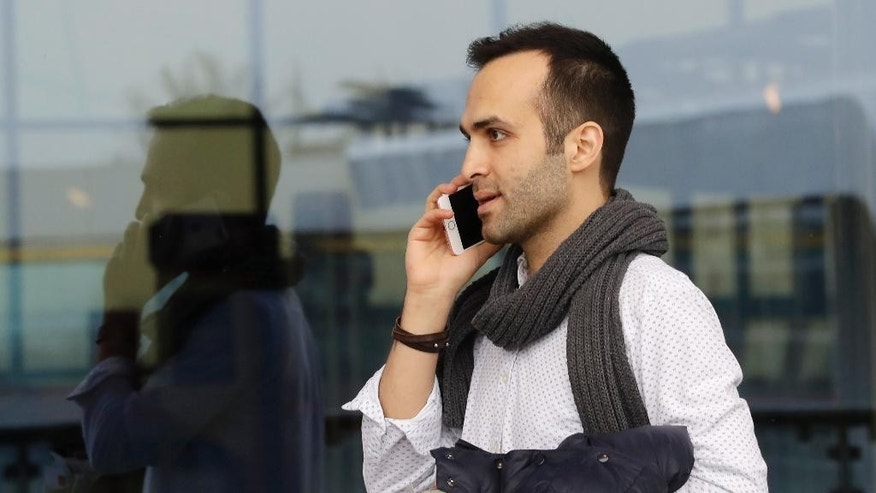 Iranian-born bioengineer researcher Nima Enayati talks on his phone at Milan's Malpensa International airport in Busto Arsizio, Italy, Sunday, Feb. 5, 2017. Just hours after an appeals court blocked an attempt to re-impose the travel ban, Iranian researcher Nima Enayati checked in on an Emirates Airline flight direct from Milan's Malpensa airport to New York's JFK on Sunday afternoon.  (AP Photo/Antonio Calanni)