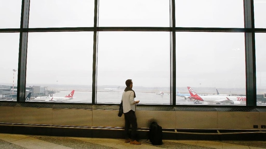 Iranian-born bioengineer researcher Nima Enayati looks out at planes at the Milan's Malpensa International airport in Busto Arsizio, Italy, Sunday, Feb. 5, 2017.  Just hours after an appeals court blocked an attempt to re-impose the travel ban, Iranian researcher Nima Enayati checked in on an Emirates Airline flight direct from Milan's Malpensa airport to New York's JFK on Sunday afternoon.  (AP Photo/Antonio Calanni)