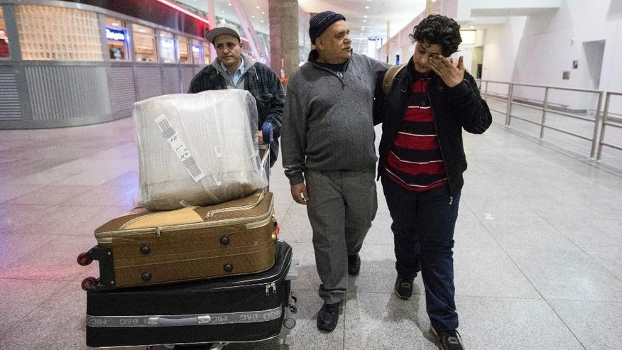Ali Abdullah Alghazali, 13, right, from Yemen, wipes his eyes as he walks with his father Abdullah Alghazali, left, and his uncle after arrival at John F. Kennedy International Airport in New York, Sunday, Feb. 5, 2017. Travelers from the seven predominantly Muslim countries affected by President Donald Trump's ban enjoyed tearful reunions with family members in the U.S. on Sunday after a federal judge swept the restrictions aside. (AP Photo/Alexander F. Yuan)