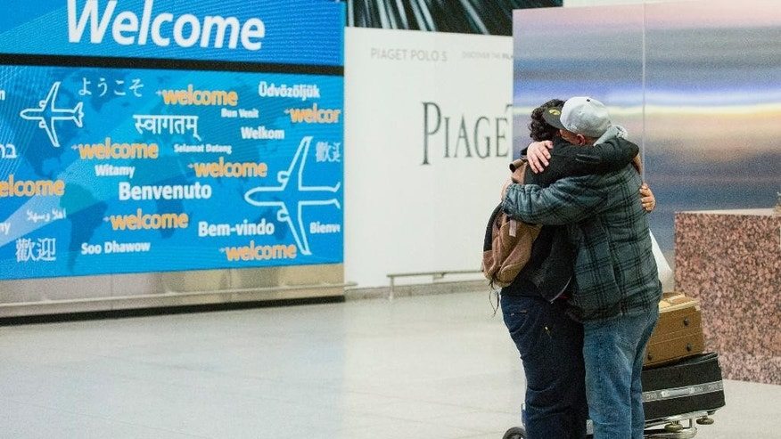 Abdullah Alghazali, right, hugs his 13-year-old son Ali Abdullah Alghazali after the Yemeni boy stepped out of an arrival entrance at John F. Kennedy International Airport in New York, Sunday, Feb. 5, 2017. Travelers from the seven predominantly Muslim countries affected by President Donald Trump's ban enjoyed tearful reunions with family members in the U.S. on Sunday after a federal judge swept the restrictions aside. (AP Photo/Alexander F. Yuan)