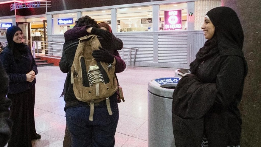 Ali Abdullah Alghazali, 13, from Yemen, center front, hugs his mother as his cousins looks on after he stepped out of an arrival entrance at John F. Kennedy International Airport, in New York, Sunday, Feb. 5, 2017. Travelers from the seven predominantly Muslim countries affected by President Donald Trump's ban enjoyed tearful reunions with family members in the U.S. on Sunday after a federal judge swept the restrictions aside. (AP Photo/Alexander F. Yuan)