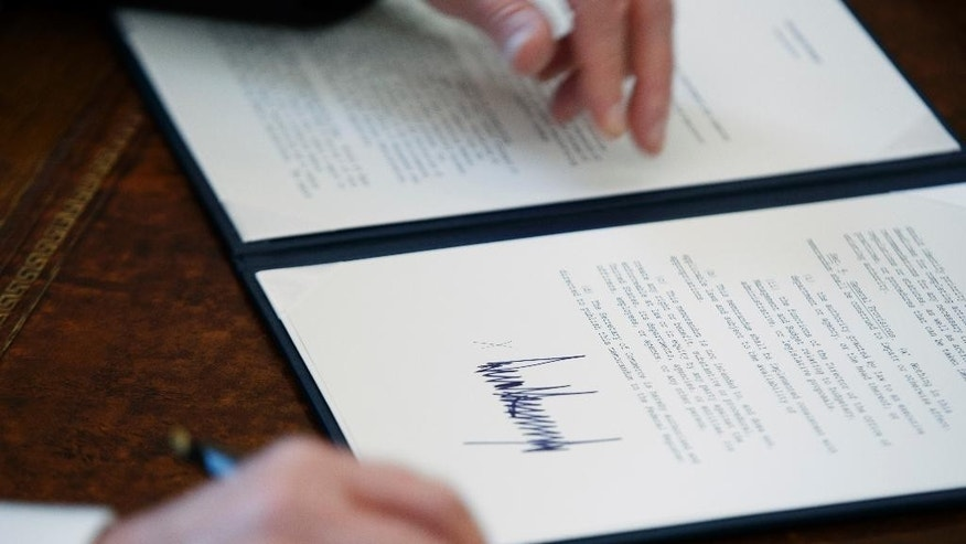 FILE - In this Jan. 24, 2017, file photo, the signature of President Donald Trump is seen on an executive order in Oval Office of the White House in Washington. Trump has taken 18 executive actions since being sworn into office on Jan. 20. Some of the papers he signed were executive orders that dealt with building the wall he promised along the U.S.-Mexico border; temporarily banning entry to the U.S. by refugees and people from seven majority-Muslim nations; and beginning to chip away at the Affordable Care Act. (AP Photo/Evan Vucci, File)