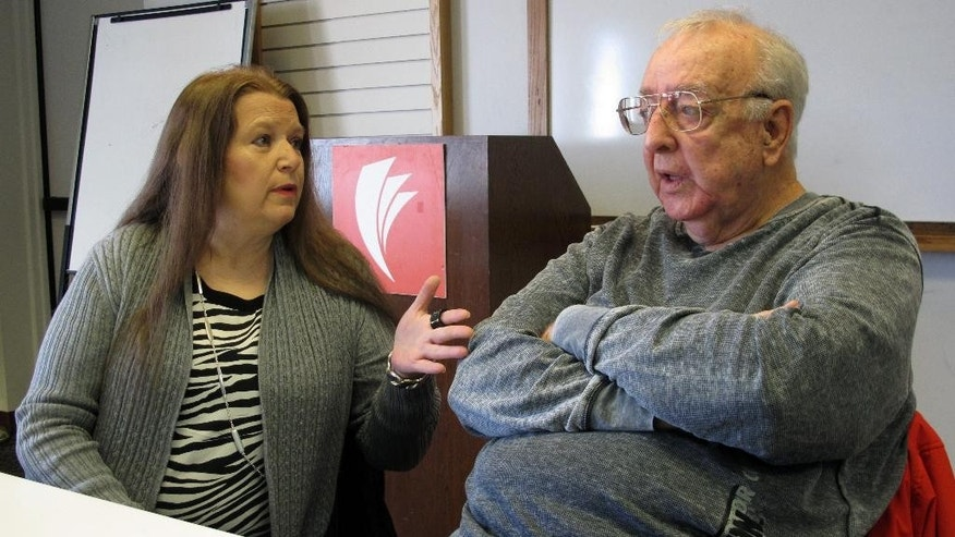 In this Monday, Jan. 30, 2017, photo, Lori Cooper, left, discusses her efforts to bring to trial the suspect who shot her father, Columbus police officer Niki Cooper, in 1972, as Niki Cooper and partner Bob Stout, right, interrupted a burglary,  in Columbus, Ohio. After her father's death three years earlier, Lori Cooper discovered the 82-year-old suspect was alive and living in Dayton, Ohio, about an hour away. (AP Photo/Andrew Welsh-Huggins)