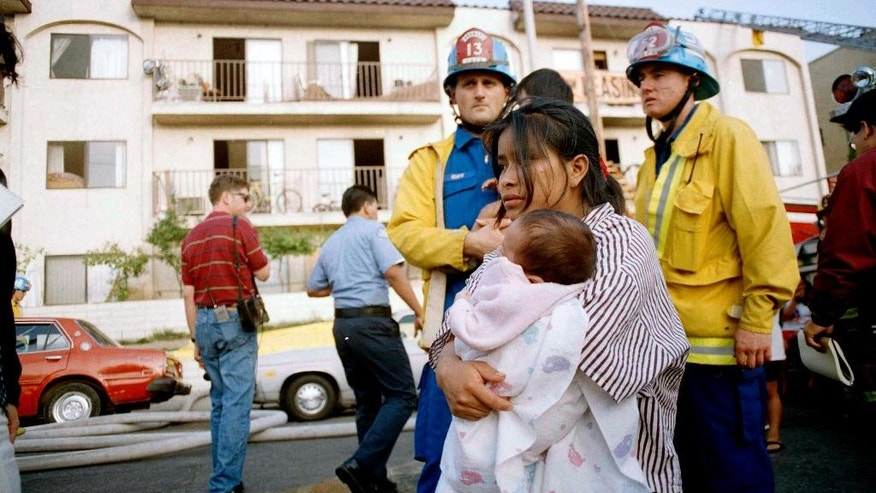 FILE -  In this May 3, 1993, file photo, May Isabela Diego holds her infant son Pedro in the aftermath of a fire in an apartment complex in the Westlake section of Los Angeles. Diego had to drop her two children out of a window as fire threatened their safety. Police have arrested several people for the 1993 fire that killed 10 people, including seven children. (AP Photo/Michael Tweed, File)