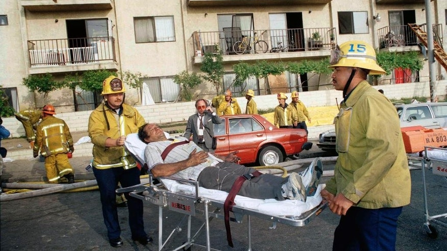 FILE - In this May 3, 1993, file photo, a survivor of an apartment complex fire is wheeled to an ambulance by Los Angeles Fire Department personnel near downtown Los Angeles. Los Angeles Police Chief Charlie Beck will announce details of arrests made in connection with the 1993 fire that killed 10 people, including seven children. Officials said that several arrests were made recently and the people remain jailed. (AP Photo/Doug Pizac,File)
