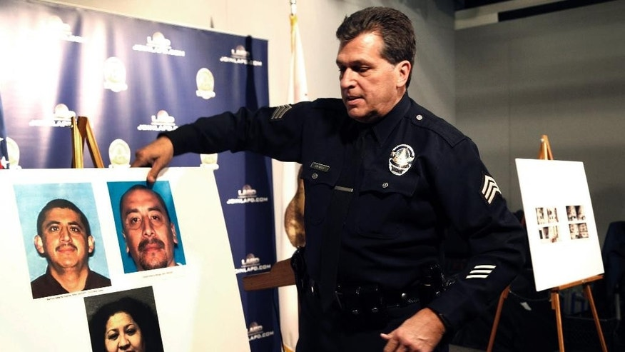 Los Angeles police Sgt. Jack Richter displays photos of arson suspects from a 1993 fire prior to a news conference in Los Angeles, Monday, Feb. 6, 2017. Los Angeles police say three people are in custody and a fourth is being sought in connection with a deadly fire that struck an apartment building in 1993. Two men were arrested Feb. 3 and a woman was already in custody in connection with the fire. Police will ask the district attorney to file homicide charges with special circumstances involving multiple victims, gang affiliations and arson. (AP Photo/Nick Ut)