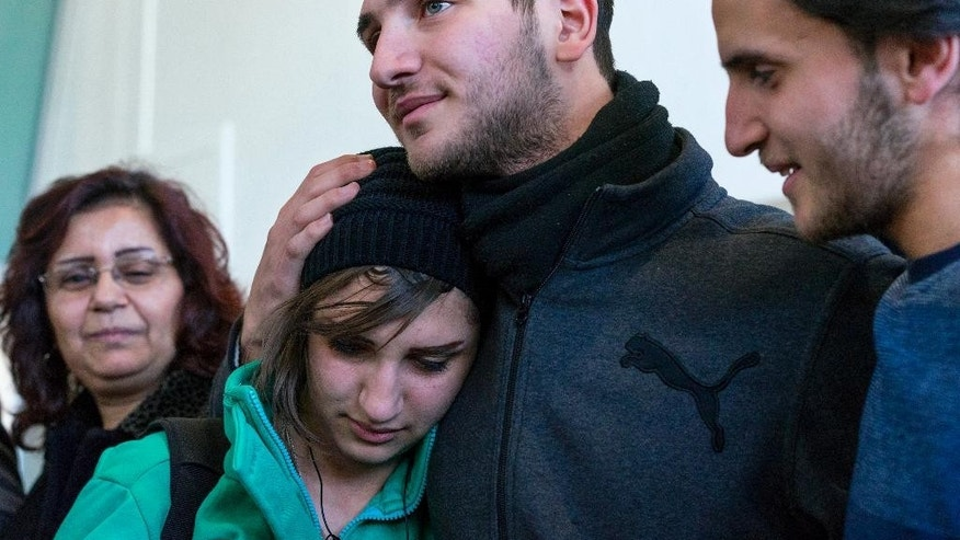 Tawfik Assali, 21, center, of Allentown, Pa., embraces his sister Sarah Assali, 19, upon her and other family members' arrival from Syria at John F. Kennedy International Airport in New York, Monday, Feb. 6, 2017. Right is Mathew Assali, 17, who arrived today. Attorneys said Dr. Assali's brothers, their wives and their two teenage children returned to Syria after they were denied entrance to the United States on Jan. 28 although they had visas in hand after a 13-year effort. (AP Photo/Craig Ruttle)