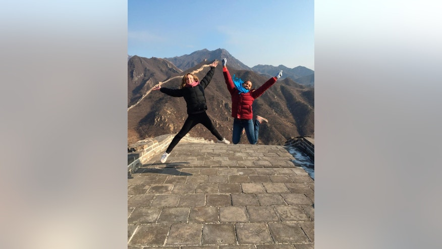 This undated photo provided by Youth For Understanding USA shows YFU exchange student Maya Hammond, right, jumping for a photo while hiking the Great Wall of China in Beijing for the first time with her European classmate. (Maya Hammond/Youth For Understanding via AP)