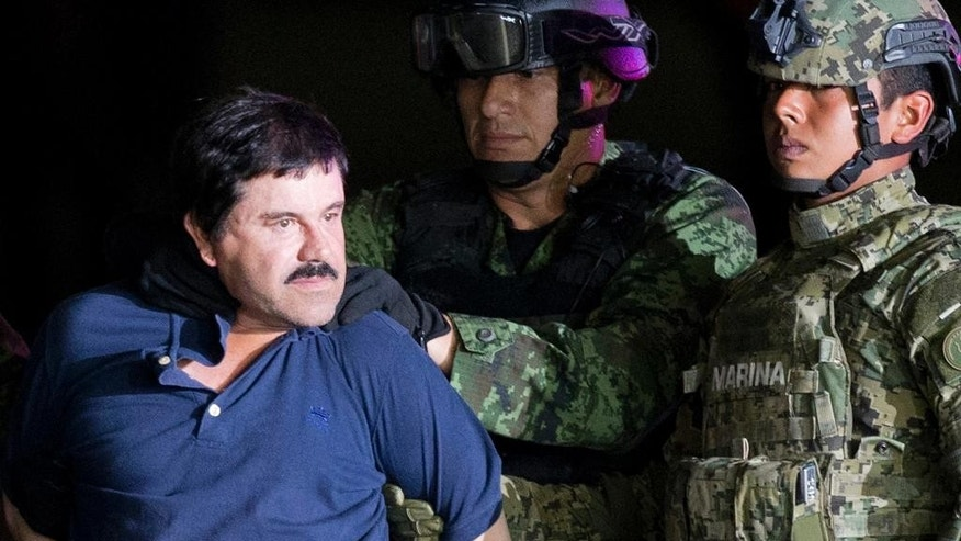 "FILE - In this Jan. 8, 2016 file photo, a handcuffed Joaquin ""El Chapo"" Guzman is made to face the press as he is escorted to a helicopter by Mexican soldiers and marines at a federal hangar in Mexico City. Guzman is scheduled to appear in person in a federal court in New York. A judge initially ruled that Guzman would appear in court by video on Friday, Feb. 3, rather than have marshals escort him to and from a high-security Manhattan jail cell. The order was changed after his lawyers asked the judge to reconsider. (AP Photo/Eduardo Verdugo, File)"
