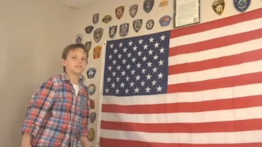 Jacob Rieger with badges sent to him from police departments across the country.