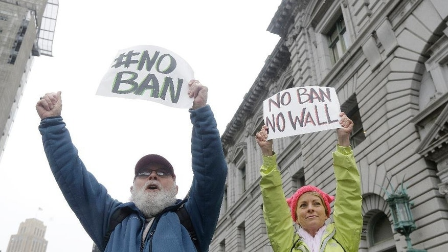 David Pearce, left, and his daughter Crissy Pearce hold signs outside of the 9th U.S. Circuit Court of Appeals in San Francisco, Tuesday, Feb. 7, 2017. President Donald Trump's travel ban faced its biggest legal test yet Tuesday as a panel of federal judges prepared to hear arguments from the administration and its opponents about two fundamentally divergent views of the executive branch and the court system. (AP Photo/Jeff Chiu)