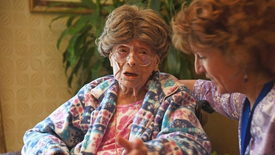 In this July 19, 2016, file photo, 113-year-old Adele Dunlap, left, talks with Susan Dempster, right, the activities director at the Country Arch Care Center in Pittstown, N.J.