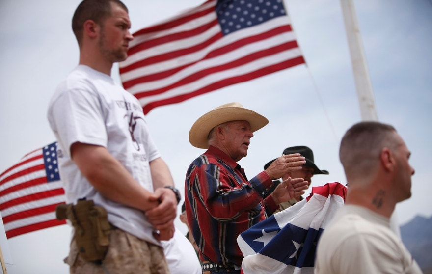 FILE - In this April 18, 2014, file photo, rancher Cliven Bundy, flanked by armed supporters, speaks at a protest camp near Bunkerville, Nev. Supporters of cattleman and anti-federal figure Cliven Bundy are protesting a presidential decision to give national monument protection to public land where Bundy grazes cows near his southern Nevada ranch. (John Locher/Las Vegas Review-Journal via AP, File)