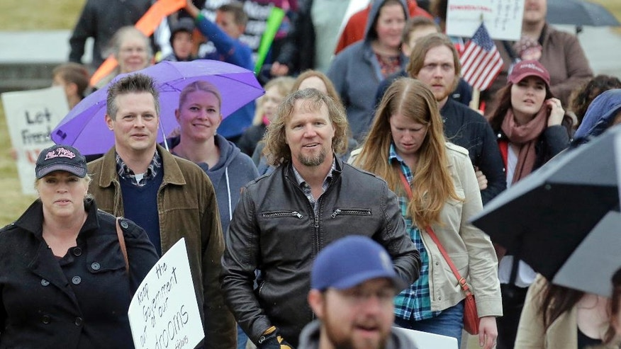 "Kody Brown, center, from TV's reality show ""Sister Wives,"" marches during a protest at the state Capitol Friday, Feb. 10, 2017, in Salt Lake City. Several hundred people in polygamist relationships say they want Utah lawmakers and law enforcement officials to know that they're not going away and should be allowed the freedom to practice their plural marriages.  (AP Photo/Rick Bowmer)"