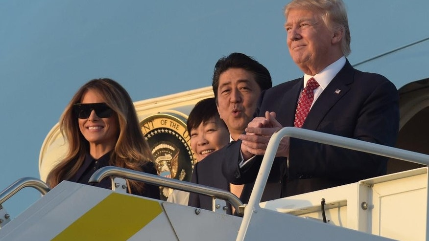 President Donald Trump, right, Japanese Prime Minister Shinzo Abe, second from right, and their spouses, first lady Melania Trump, left, and Akie Abe, second from left, stand at the top of Air Force One at West Palm Beach International Airport in West Palm Beach, Fla., Friday, Feb. 10, 2017. The Trumps are hosting the Abes at their Mar-a-Lago estate in Palm Beach for the weekend. (AP Photo/Susan Walsh)