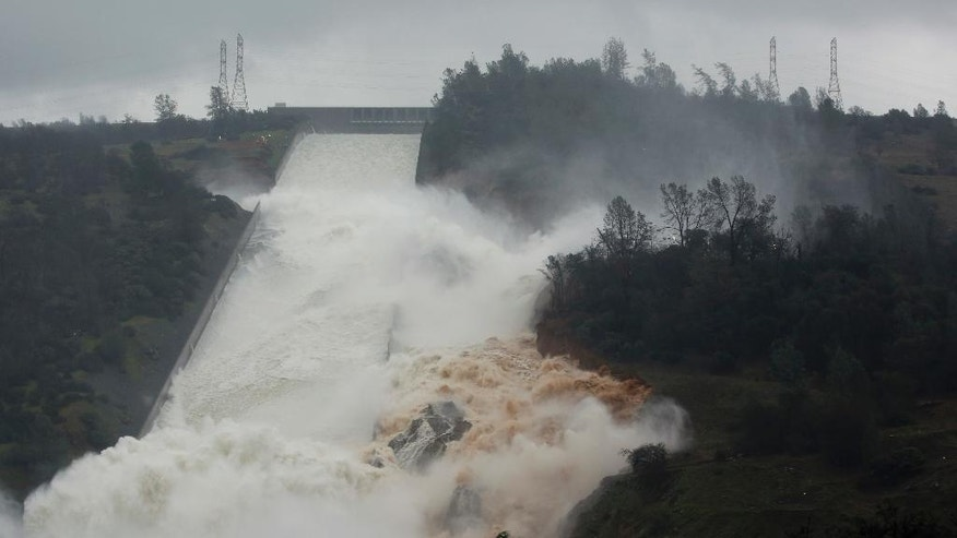 "Water flows through break in the wall of the Oroville Dam spillway, Thursday, Feb. 9, 2017, in Oroville, Calif. The torrent chewed up trees and soil alongside the concrete spillway before rejoining the main channel below. Engineers don't know what caused what state Department of Water Resources spokesman Eric See called a ""massive"" cave-in that is expected to keep growing until it reaches bedrock. (AP Photo/Rich Pedroncelli)"